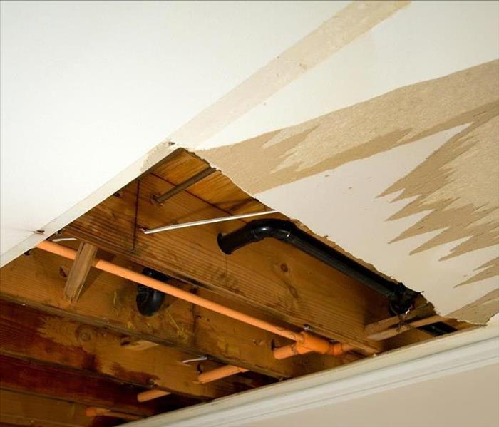 An open ceiling with exposed piping and water damage.