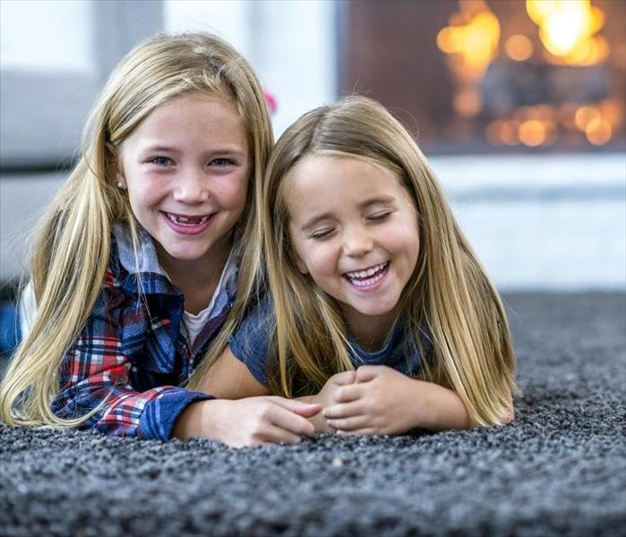 Two girls laying an carpeted floor